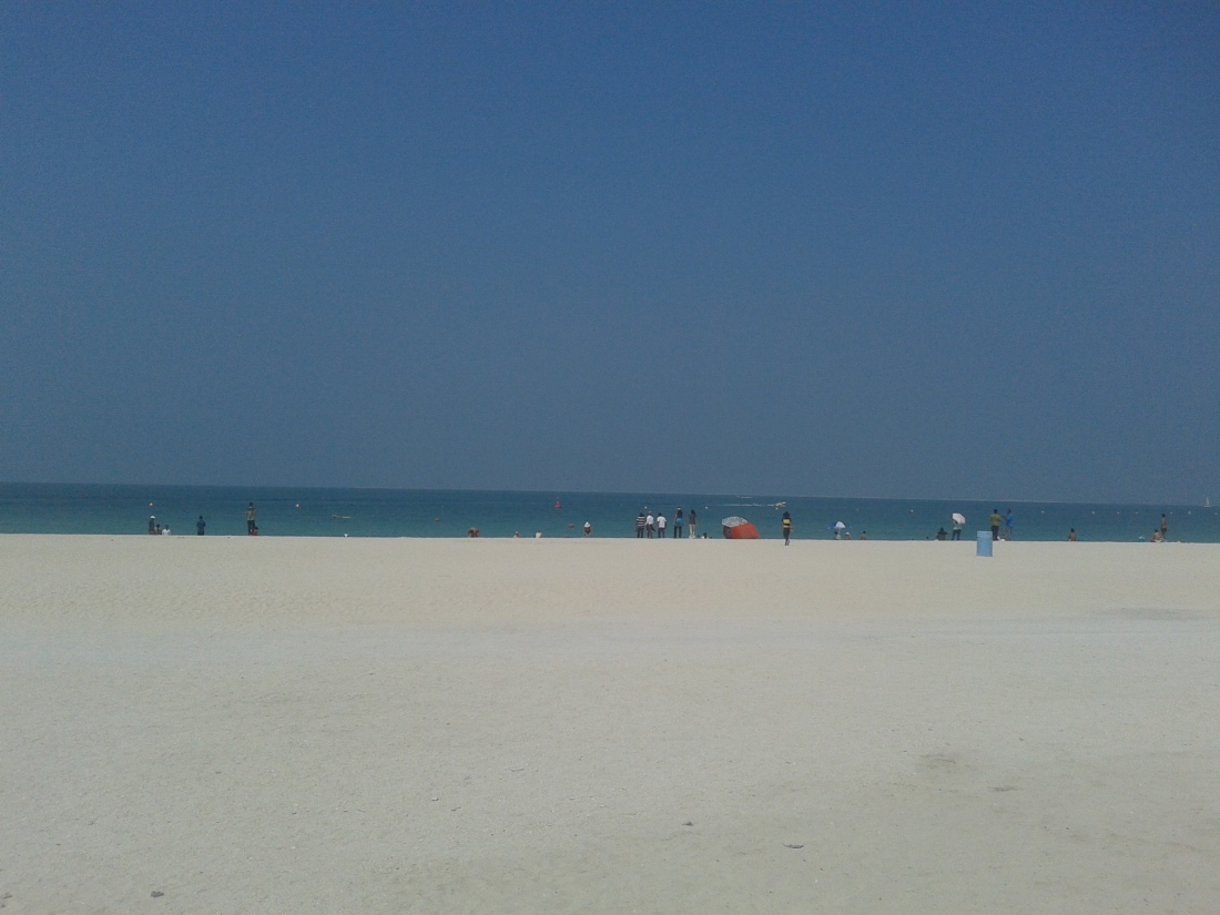 The blue Arabian sea and whitesh sand at the Jumeirah beach. Great as a wallpaper!